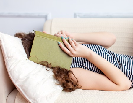 Young woman is lying on the sofa and reading book photo