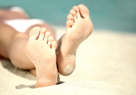 Womans feet on the white sand near the sea. photo