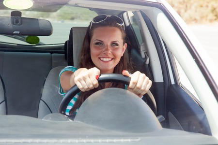 Happy young woman is driving a car Foto de archivo