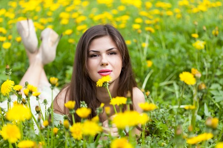 Young woman is lying on field with dandelions
