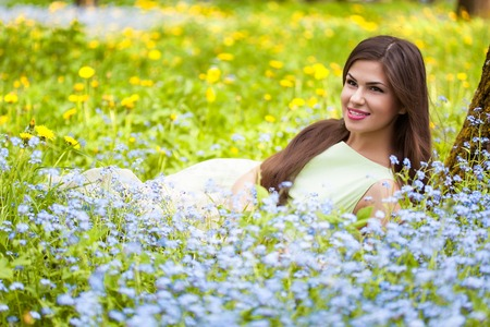 Young woman is lying on field with forget-me-not photo