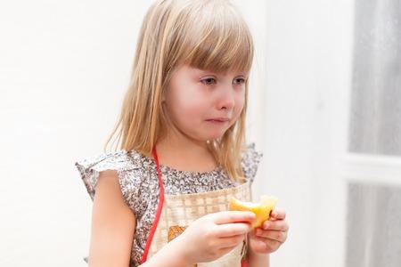 fille qui pleure: Portrait de jeune fille pleurant avec morceau de pomme dans ses mains