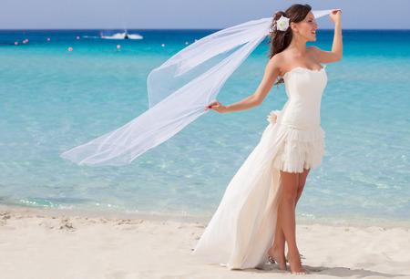 bride veil: Beautiful bride is walking on the beach Stock Photo