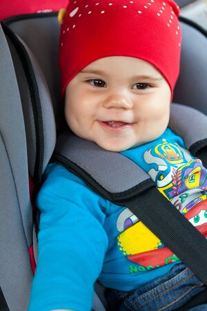 smiley face car: Portrait of cute smiling little girl sitting in her car safety seat