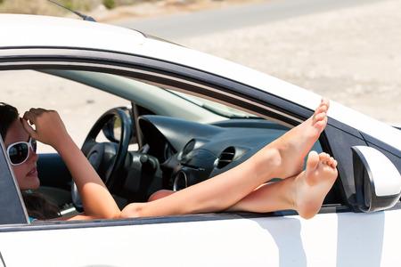 dangling: Womans legs dangling out a car window