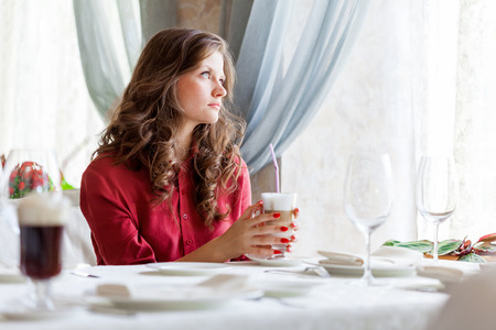 non alcoholic: A smiling woman in a restaurant is drinking latte