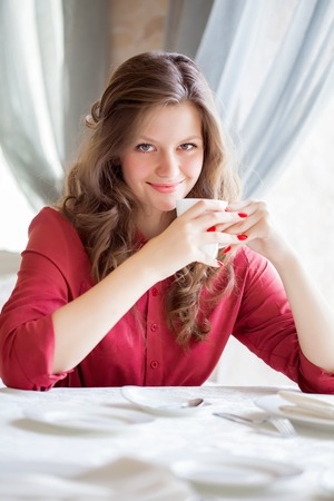 non alcoholic: A smiling woman in a restaurant is drinking coffee