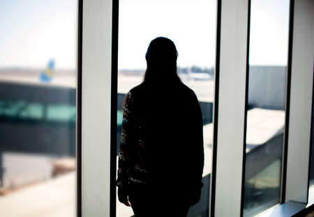 back gate: Silhouette of a woman looking at the airport landing ground