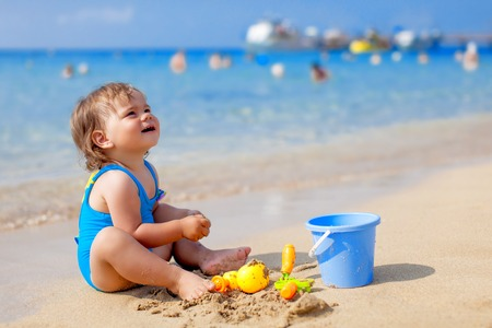 little girl beach: Little child girl in blue swimsuit is playing on the beach near blue sea Stock Photo