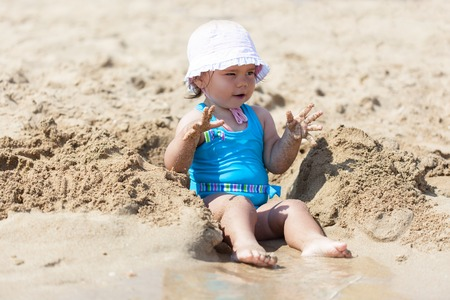 little girl swimsuit: Little child girl in blue swimsuit is playing on the beach near blue sea Stock Photo