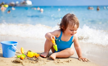 children swimsuit: Little child girl in blue swimsuit is playing on the beach near blue sea Stock Photo