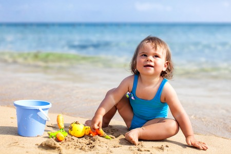 white girl: Little child girl in blue swimsuit is playing on the beach near blue sea Stock Photo