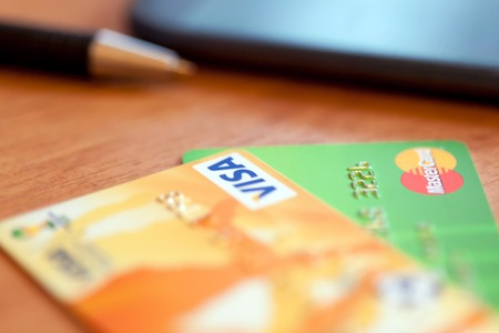 mastercard: RUSSIA, OREL -  NOVEMBER 2015: Two credit cards of Mastercard and Visa, pen and phone on the table. Soft focus