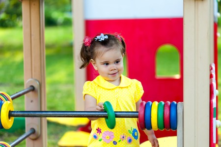 smiling little girl is playing in the park. She has fun on carousel Stock Photo