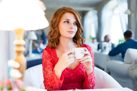 espresso cup: Portrait of happy red haired woman in red dress with mug of coffee in her hands