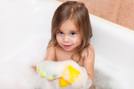 Funny baby girl playing with water and foam Stock Photo