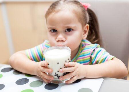 niños desayunando: Little girl having breakfast with milk kitchen