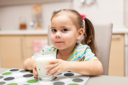 niños desayunando: La niña que tiene el desayuno con leche cocina Foto de archivo