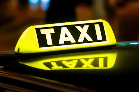 Taxi sign on the roof of a car Stock Photo
