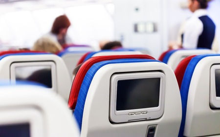 Row of seats with monitors inside of aircraft Zdjęcie Seryjne