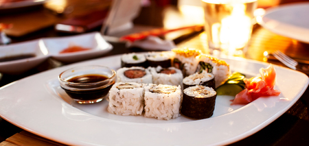White plate wit set of sushi rolls in a restaurant. Japanese cuisine