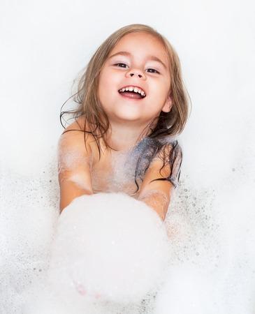 happy little girl is taking a bath with a foam