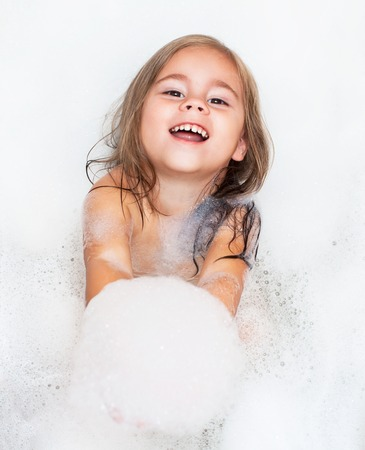 happy little girl is taking a bath with a foam
