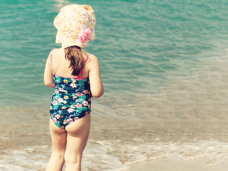 A cute little girl playing on the sea beach