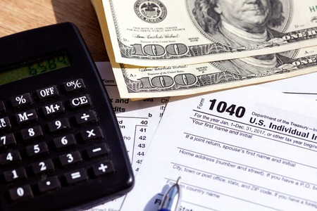 US tax form 1040 with pen and calculator. Close-up Stock Photo