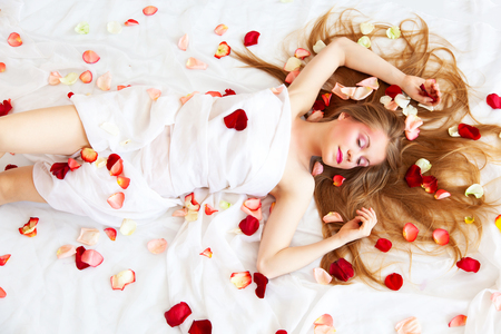 Beautyful girl with long hair relaxing on white sheets with rose petals