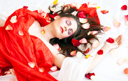 Beautyful sexy girl with long hair relaxing on white sheets with rose petals Foto de archivo - 110030000