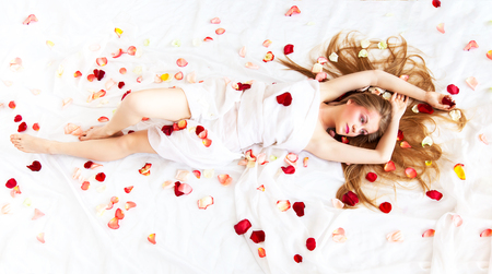 Beautyful sexy girl with long hair relaxing on white sheets with rose petals Foto de archivo - 110030035