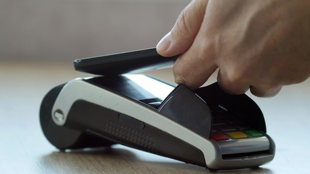 Customer paying with NFC technology by mobile phone on POS terminal Stock Photo