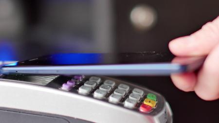 Kunde bezahlt mit NFC-Technologie per Handy am Terminal. Standard-Bild