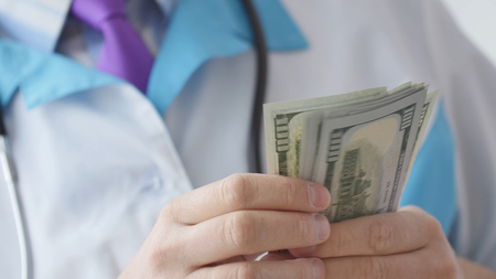 Corrupted medical doctor counting money.