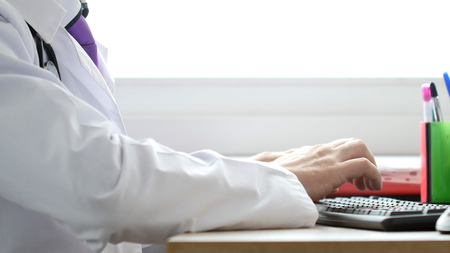 Medical doctor working on laptop in his cabinet and clicking computer mouse. Imagens