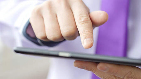Man hand touching screen on modern digital tablet pc. Close-up image with shallow depth of field. Concept of modern gadgets in use