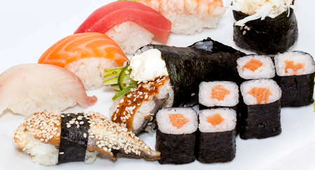 Top view on sushi set isolated over white background. Plate with rolls close-up. Concept of Japanese food