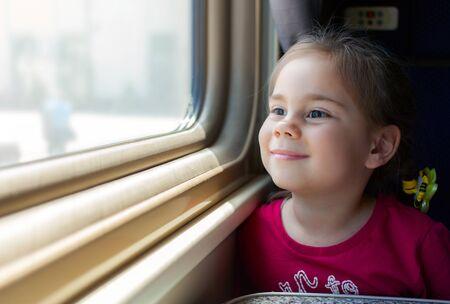 Happy little girl traveling by train. 写真素材