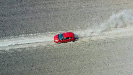 Aerial view from drone on a red car driving along the empty gravel road