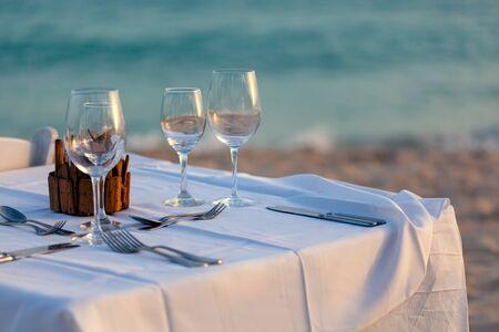 Sirviendo para una cena romántica en una playa al atardecer. Foto de archivo