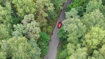 Aerial aerial view of a red car driving on country road at day. Stok Fotoğraf
