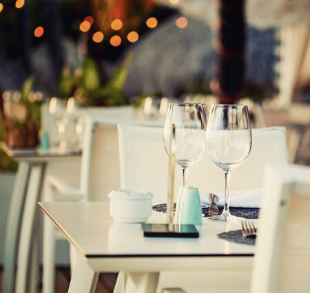Table close-up in front of street restaurant with lights background Stok Fotoğraf