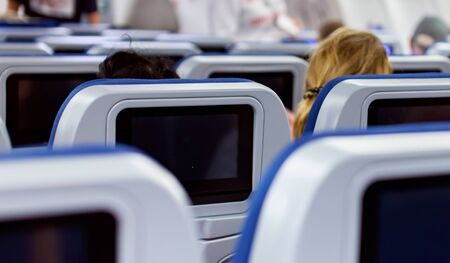 Aircraft interior with seats and blank touch screens displays.