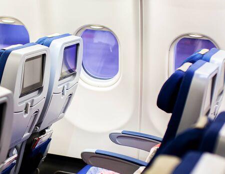 Interno dell'aereo con sedili e display touch screen vuoti. Archivio Fotografico