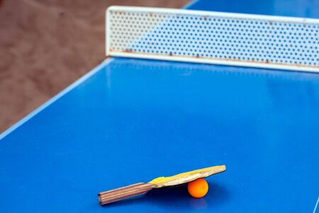 Table tennis  racket and ball on a blue table