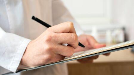Médecin de sexe masculin faisant de la paperasse au bureau.