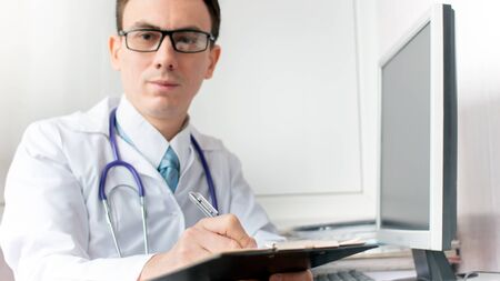 Doctor writing patient notes on a medical examination Stock Photo