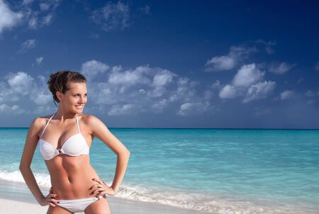 Young woman in white swimsuit bikini looking into the distance at sandy beach Foto de archivo