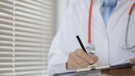 Male doctor doing paperwork in the office. Stock Photo